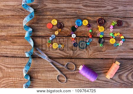 2016 written by buttons and beads on wooden background. Toned image.
