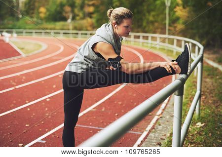 Athletic Young Woman Stretching On Stadium