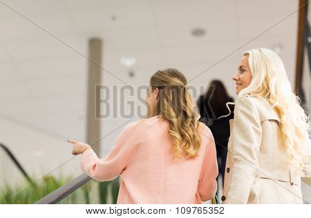 sale, consumerism and people concept - happy young women pointing finger and raising on escalator in mall