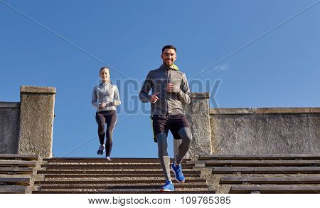 fitness, sport, people and lifestyle concept - happy couple walking downstairs on stadium