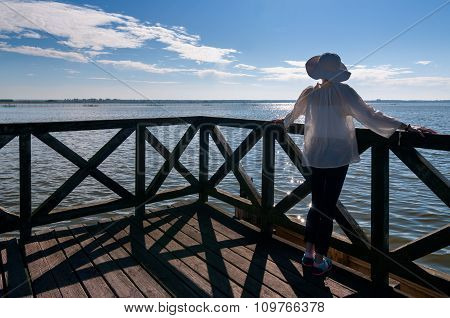 Young Woman In White Hat And Standing On Old Wooden Pier