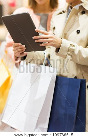 sale, consumerism, technology and people concept - close up of young women with tablet pc computer and shopping bags in mall