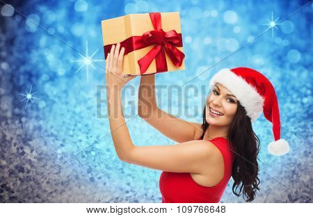 people, holidays, christmas and celebration concept - beautiful sexy woman in red dress and santa hat with gift box over blue glitter or holidays lights background