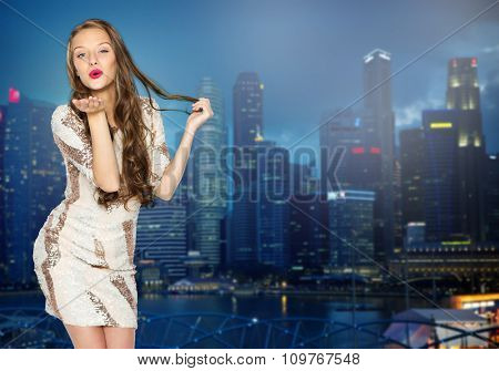 people, style, holidays, nightlife and fashion concept - happy young woman or teen girl in fancy dress with sequins and long wavy hair sending blow kiss over night singapore city background