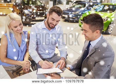 auto business, sale and people concept - happy couple with dealer buying car and signing documents in auto show or salon over snow effect