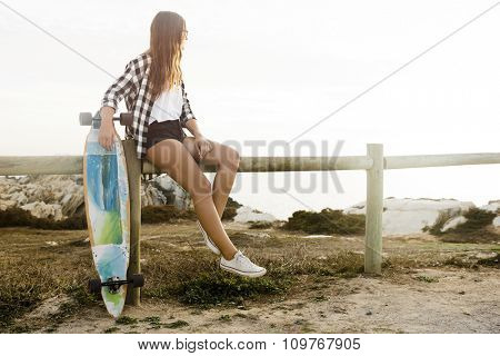 Beautiful and fashion young woman posing with a skateboard