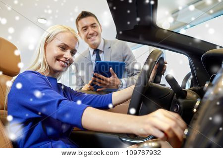 auto business, car sale, technology and people concept - happy woman and car dealer with tablet pc computer in auto show or salon over snow effect