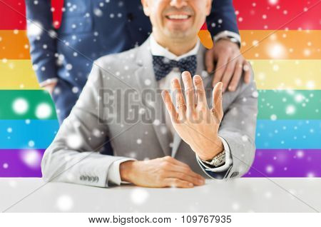 people, celebration, homosexuality, same-sex marriage and love concept - close up of male gay couple with wedding rings on putting hand on shoulder over rainbow flag background and snow effect
