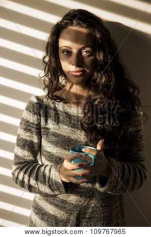 Portrait of a beautiful woman on her bedroom drinking coffee