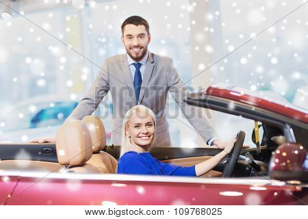 auto business, car sale, consumerism and people concept - happy couple buying cabrio car in auto show or salon over snow effect