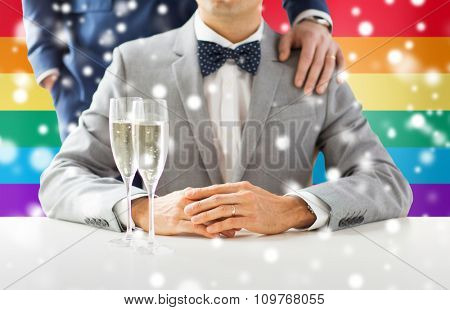people, celebration, homosexuality, same-sex marriage and love concept - close up of happy married male gay couple with sparkling wine glasses on wedding over rainbow flag background and snow effect