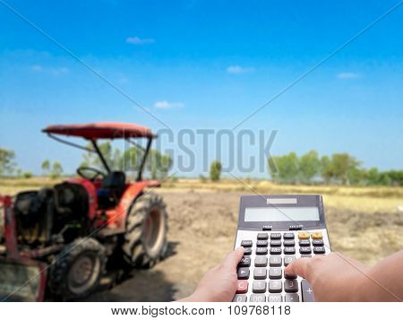 Agriculture Investment Cost Concept By Calculator And The Blur Farm And Tractor In Background