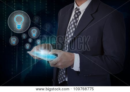 Businessman hand touch screen light bulb icons on a tablet. internet and technology concept.