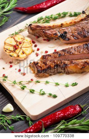 Steak with herbs, salt and and pepper on wooden background