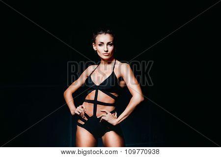 Sexy brunette posing in black lingerie on dark background.