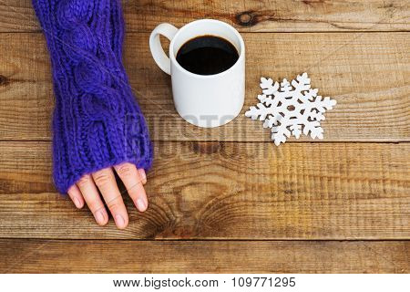 Woman Hand In Teal Glove, Mug With Hot Coffee Or Cocoa And Snowflake On Wooden Background.