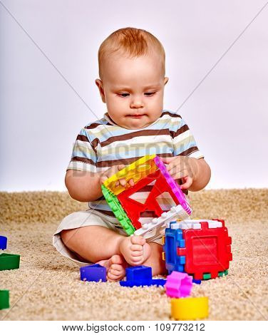Kid baby boy sitting on floor at carpet and playing with puzzle toy.