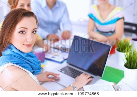 Portrait of attractive female  designer sitting on desk  in office