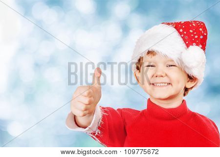 Funny Boy In A Christmas Hat  On Blue Snow Bokeh Background.