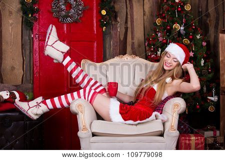 Beautiful Santa female having fun and smiling near the Christmas tree, sitting in vintage chair. New