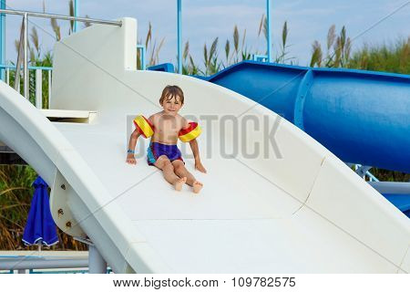 little boy having fun on waterslide pool