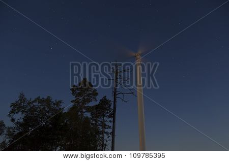 Night forest and wind turbine