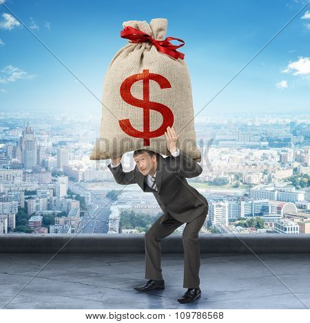 Businessman holding big moneybag