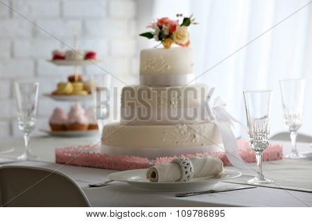 Wedding layered cake on decorated table in restaurant