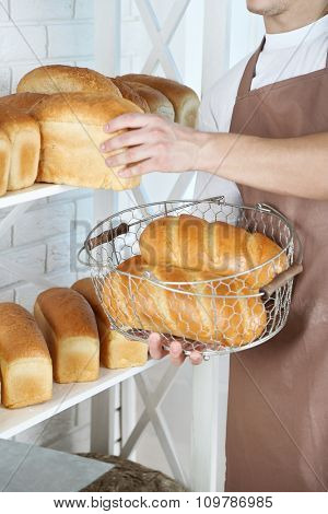 Baker holding freshly baked bread in kitchen of bakery