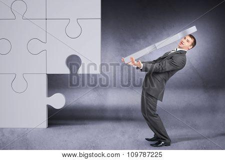 Businessman holding big puzzle piece