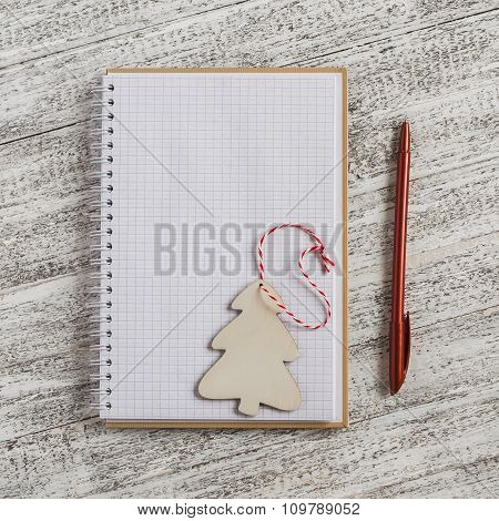 Open A Blank Notebook And Wooden Christmas Decoration - Christmas Tree On Bright Wooden Table