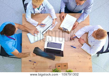 Male and female doctors working on reports in medical office