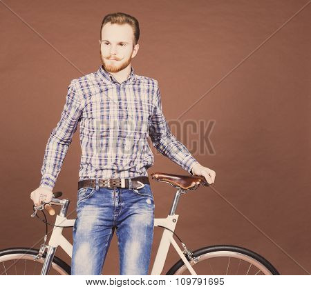 A young man with mustache and beard is near fashionable modern fixgear bicycle. Jeans and plaid shir
