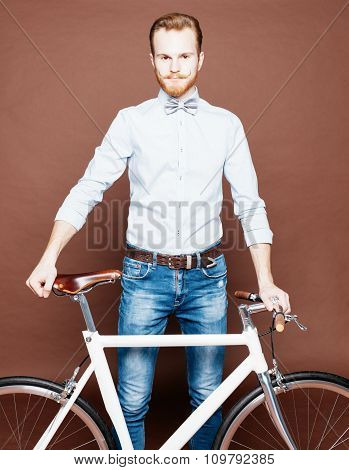A young man with mustache and beard is near fashionable modern fixgear bicycle. Jeans and shirt, the