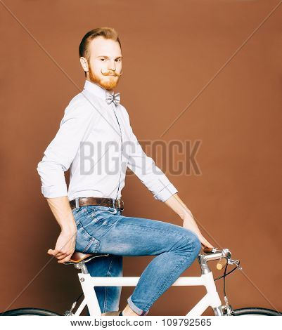 A young man with mustache and beard is sitting on a fashionable modern fixgear bicycle. Jeans and sh