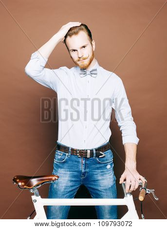 A young man with mustache and beard is near fashionable modern fixgear bicycle. Smooth hair on the h