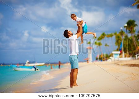Playful Father And Son Having Fun On Tropical Beach
