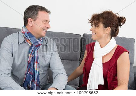 Couple Relaxing On The Couch In The Living Room And Looking At Each Other