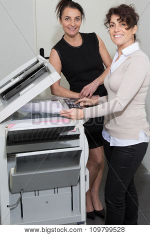 Two Woman Business Colleagues Working On Office Printer