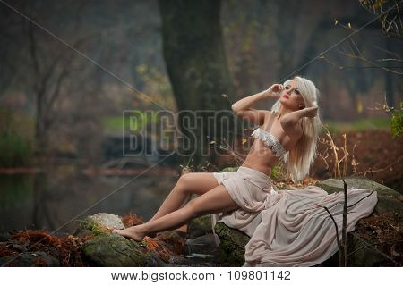 Lovely young lady sitting near river in enchanted woods. Sensual blonde with white clothes posing