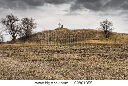 Landscape with ancient burial mound in agricultural field in central Ukrain