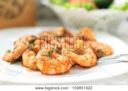 Fried black tiger prawns with herbs and spices on a white plate.
