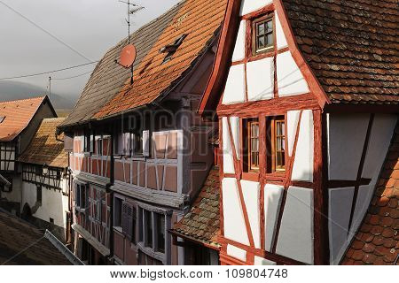 Half-timbered Houses On A Narrow Street In Eguisheim, Alsace, France