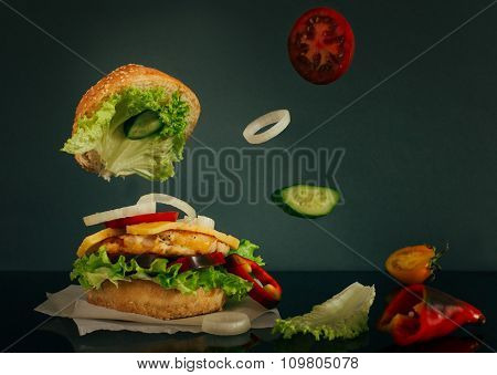 Delicious Burger With Flying Ingredients On Dark Background