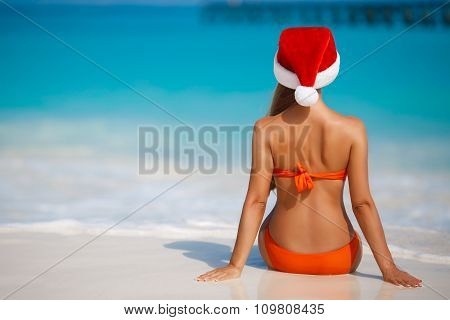 A woman on a tropical beach in the hat of Santa Claus