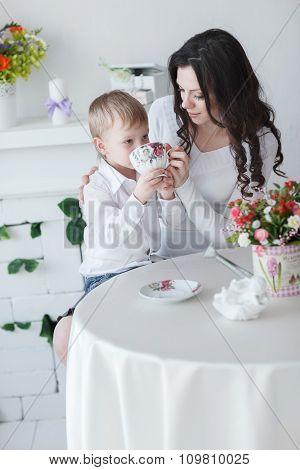 Beautiful Blond Boy Drinks Tea At Mom's