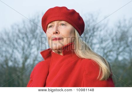 Beautiful older woman wearing a red coat and hat