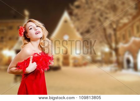 Pretty girl excited in dress on winter night urban background
