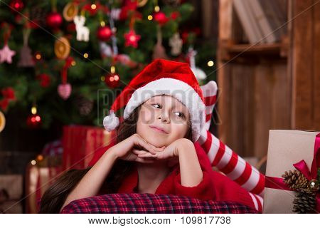Portrait of cute girl in Santa hat falling asleep under Christmas tree