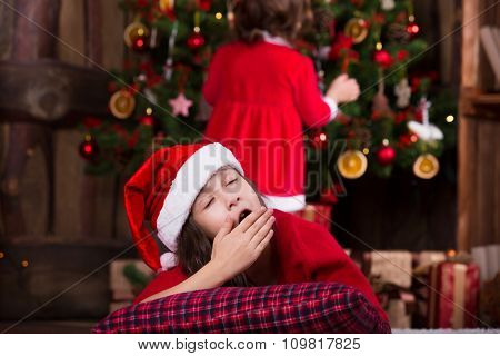 Portrait of cute girl in Santa hat fell asleep under Christmas tree when her sister find a gift
